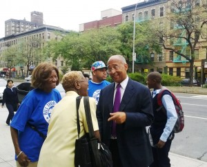 Bill Thompson greets with morning commuters entering a subway station in Harlem. Credit: Alex Ellefson